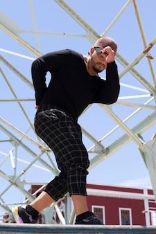 Ballerino acrobatico urbano di giovane uomo latino per strada facendo una performance.