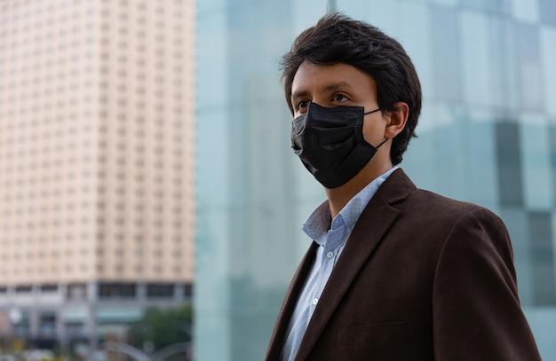 Giovane uomo latino che indossa una maschera per motivi protettivi durante la pandemia covid