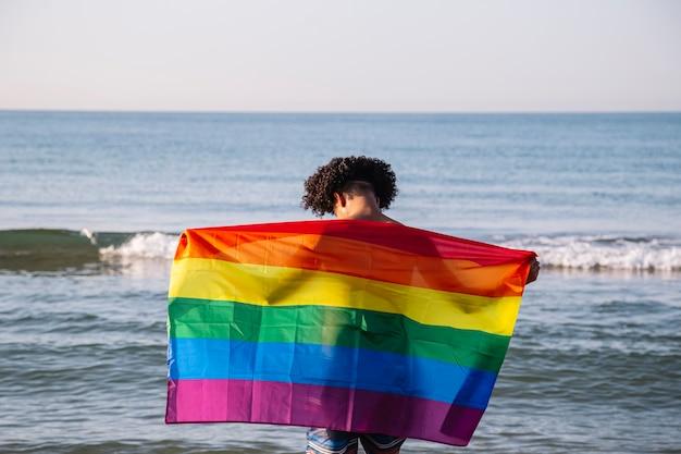 Giovane uomo latino con una bandiera lgtbi sulla spiaggia
