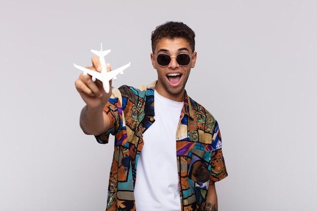 Giovane uomo latino con un aereo. concetto di viaggio