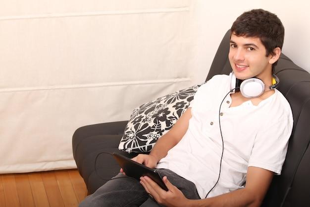Un giovane uomo latino con un tablet pc e le cuffie sul divano