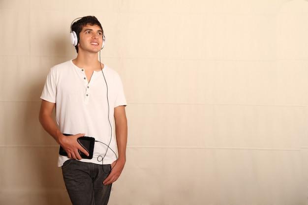 Un giovane uomo latino con un tablet pc e le cuffie