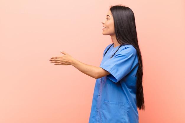 Giovane infermiera latina che sorride, ti saluta e ti offre una stretta di mano per chiudere un affare riuscito, concetto di cooperazione contro la parete rosa