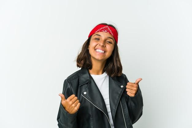 La giovane donna latina dell'attuatore isolata su fondo bianco strizza l'occhio e tiene un gesto giusto con la mano.