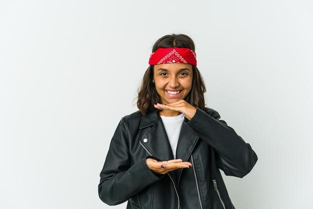 Giovane donna latina dell'attuatore isolata su uno spazio bianco che tiene qualcosa con le palme, offrendo alla macchina fotografica.