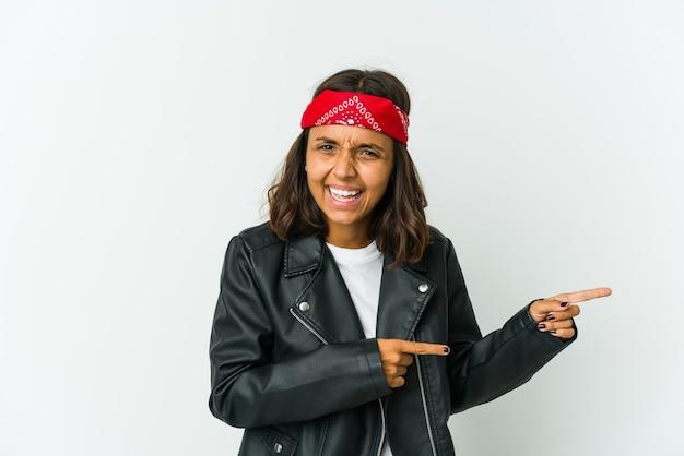 Giovane donna latina rocker isolata sul muro bianco che guarda lontano tenendo la mano sulla fronte.