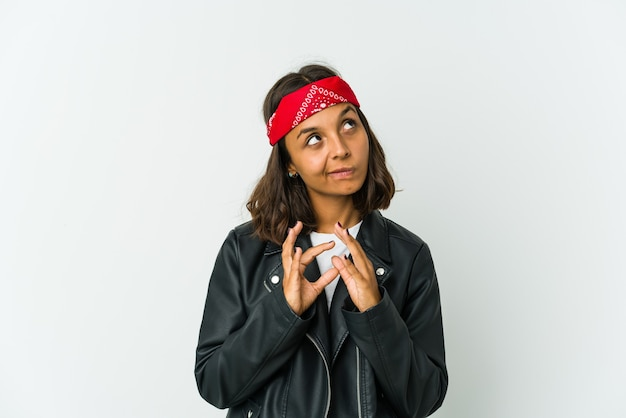 Giovane donna latina dell'attuatore isolata sulla parete bianca che mostra uno spazio della copia su una palma e che tiene un'altra mano sulla vita.