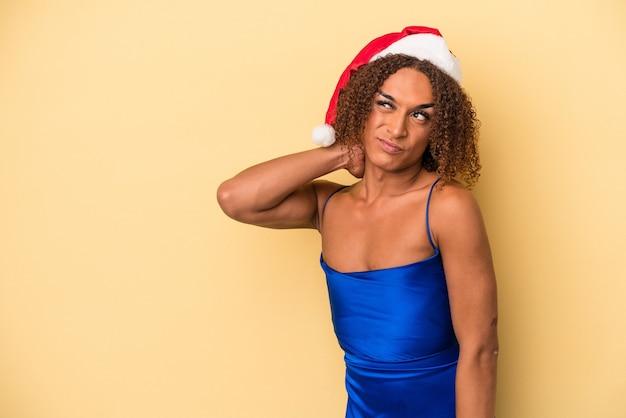 Giovane donna transessuale latina che celebra il natale isolato su sfondo giallo toccando la parte posteriore della testa, pensando e facendo una scelta.