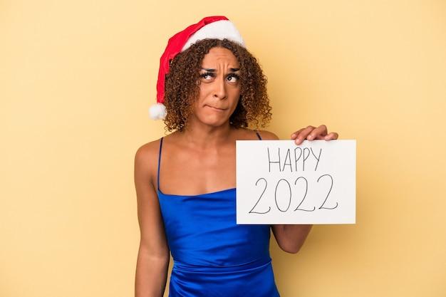 La giovane donna transessuale latina che celebra il nuovo anno isolata su sfondo giallo confusa, si sente dubbiosa e insicura.
