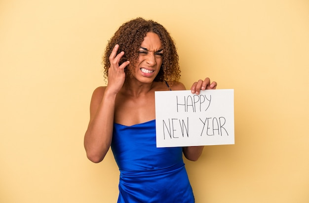 Giovane donna transessuale latina che celebra il nuovo anno isolato su sfondo giallo che copre le orecchie con le mani.