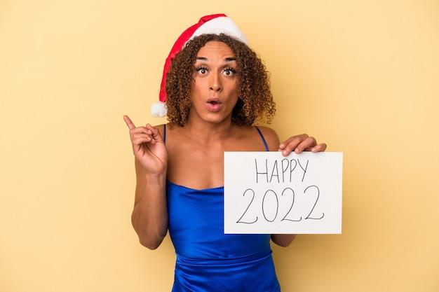 Giovane donna transessuale latina che celebra il nuovo anno isolato su sfondo giallo con qualche grande idea, concetto di creatività.