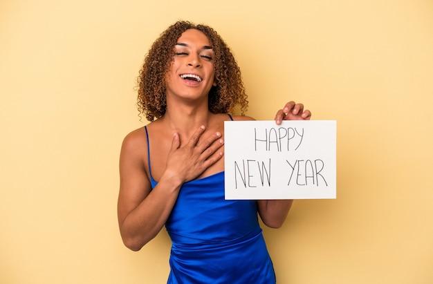 La giovane donna transessuale latina che celebra il nuovo anno isolata su sfondo giallo ride ad alta voce tenendo la mano sul petto.