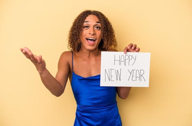 Giovane donna transessuale latina che celebra il nuovo anno isolata su sfondo giallo ricevendo una piacevole sorpresa, eccitata e alzando le mani.
