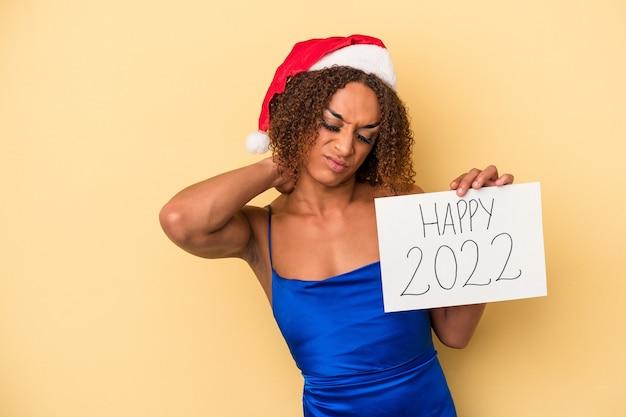 Giovane donna transessuale latina che celebra il nuovo anno isolata su sfondo giallo toccando la parte posteriore della testa, pensando e facendo una scelta.