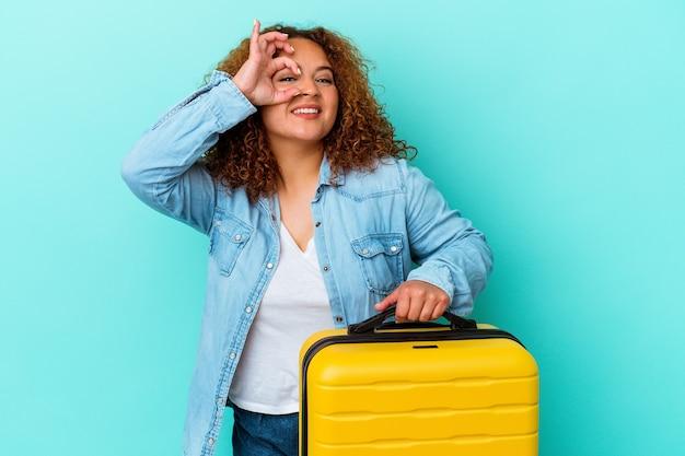 Giovane donna curvy del viaggiatore latino che tiene una valigia isolata su fondo blu eccitata mantenendo il gesto giusto sull'occhio.