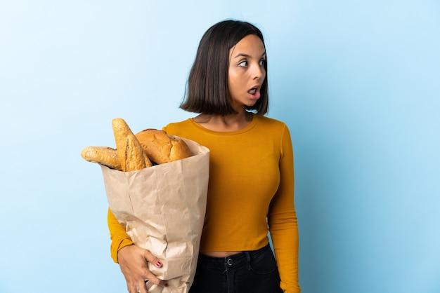Giovane donna latina che compra alcuni pani isolati sull'azzurro che fa gesto di sorpresa mentre osservava al lato