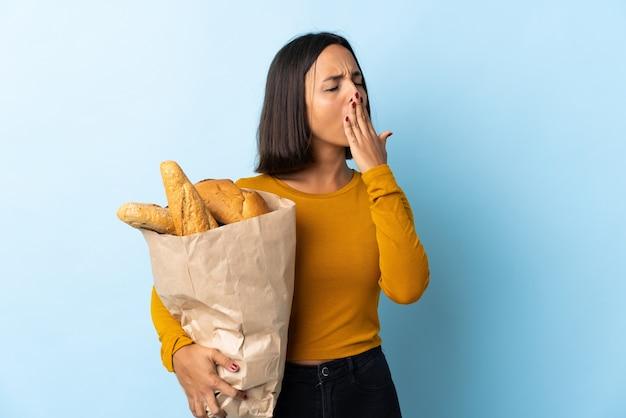 Giovane donna latina che compra alcuni pani isolati