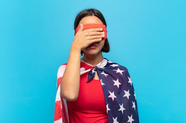 Giovane donna latina che copre gli occhi con una mano sentendosi spaventata o ansiosa, chiedendosi o aspettando ciecamente una sorpresa