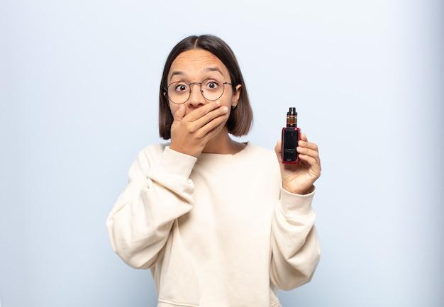 Giovane donna latina che copre la bocca con le mani con un'espressione scioccata e sorpresa, mantenendo un segreto o dicendo oops