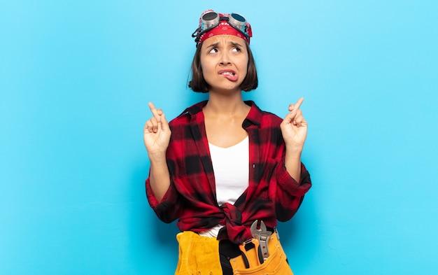 Giovane donna latina incrociando le dita ansiosamente e sperando in buona fortuna con uno sguardo preoccupato