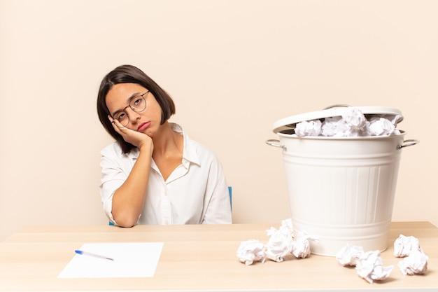 Giovane donna latina che si sente annoiata, frustrata e assonnata dopo un compito noioso, noioso e noioso, tenendo la faccia con la mano