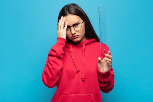 Giovane donna latina che si sente annoiata, frustrata e assonnata dopo un compito noioso, noioso e noioso, tenendo il viso con la mano