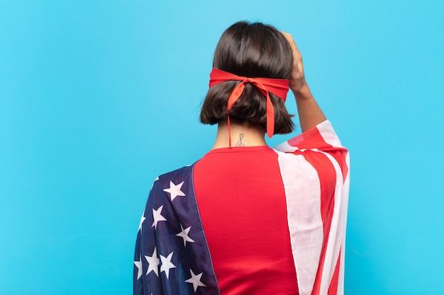 Giovane donna latina che si sente incapace e confusa, pensando a una soluzione, con una mano sul fianco e l'altra sulla testa, vista posteriore
