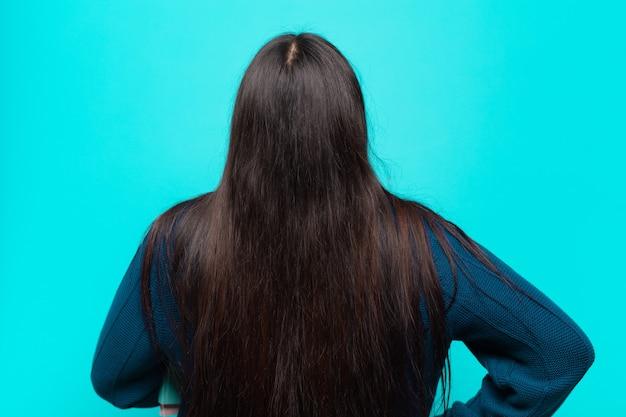 Giovane donna latina che si sente confusa o piena o dubbi e domande, chiedendosi, con le mani sui fianchi, vista posteriore