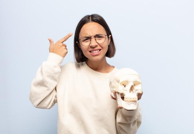 Giovane donna latina che si sente confusa e perplessa, dimostrando che sei pazzo, pazzo o fuori di testa