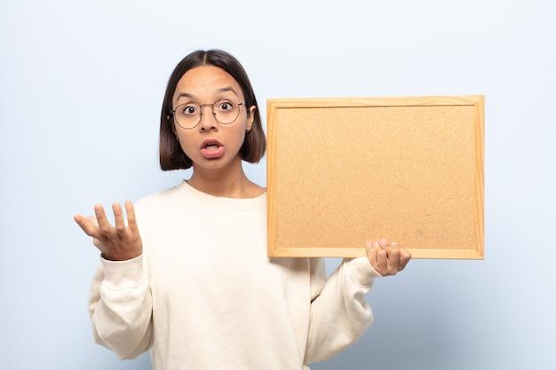 Giovane donna latina che si sente estremamente scioccata e sorpresa, ansiosa e in preda al panico, con uno sguardo stressato e inorridito