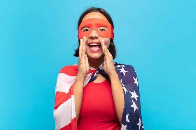 Giovane donna latina che si sente felice, eccitata e positiva, gridando con le mani vicino alla bocca, chiamando