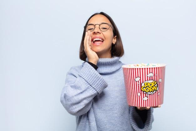 Giovane donna latina che si sente felice, eccitata e positiva, dando un grande grido con le mani vicino alla bocca, chiamando