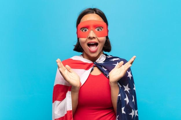Giovane donna latina che si sente felice, eccitata, sorpresa o scioccata, sorridente e stupita da qualcosa di incredibile