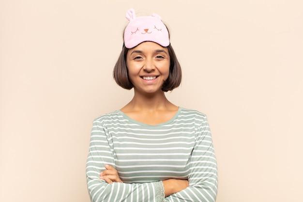 Giovane donna latina che si sente felice, orgogliosa e piena di speranza, chiedendosi o pensando, alzando lo sguardo per copiare lo spazio con le braccia incrociate
