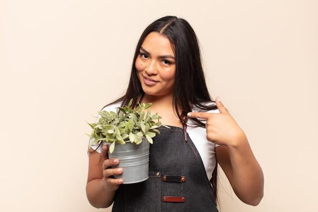 Giovane donna latina che si sente felice, sorpresa e orgogliosa, indicando se stessa con uno sguardo eccitato e stupito