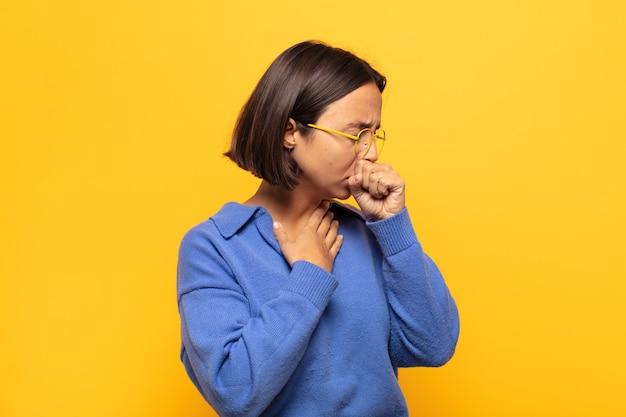 Giovane donna latina che si sente male con mal di gola e sintomi influenzali, tosse con la bocca coperta