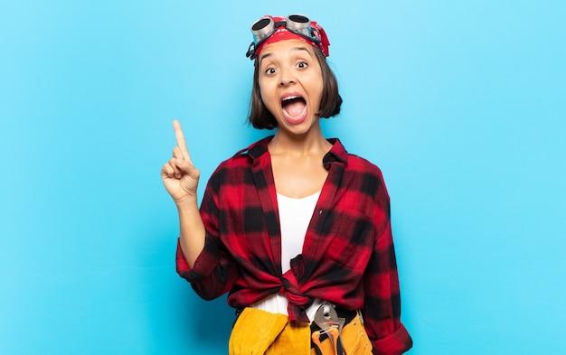 Giovane donna latina che si sente come un genio felice ed eccitato dopo aver realizzato un'idea, alzando allegramente il dito, eureka!