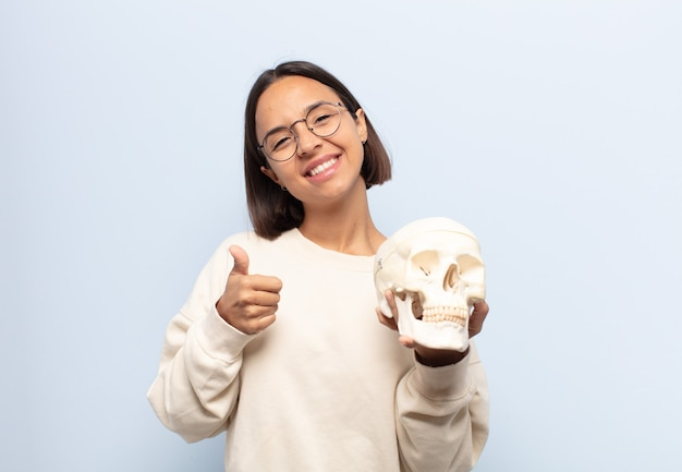 Giovane donna latina che si sente orgogliosa, spensierata, sicura di sé e felice, sorridendo positivamente con il pollice in alto Foto Premium