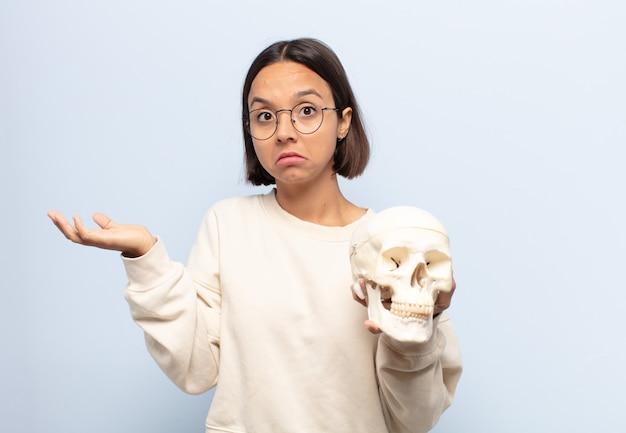 Giovane donna latina che si sente perplessa e confusa, dubita, appesantisce o sceglie diverse opzioni con un'espressione divertente