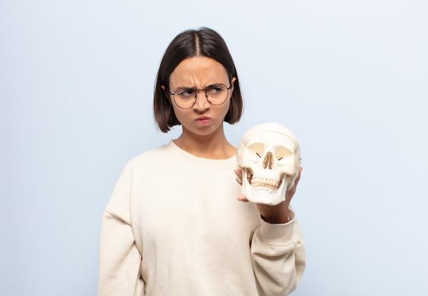 Giovane donna latina che si sente triste, turbata o arrabbiata e guarda di lato con un atteggiamento negativo, accigliata in disaccordo