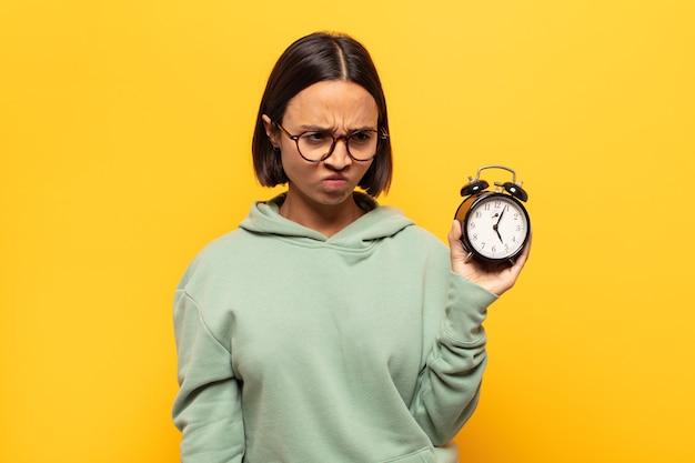 Giovane donna latina che si sente triste, sconvolta o arrabbiata e guarda di lato con un atteggiamento negativo, aggrottando la fronte in disaccordo
