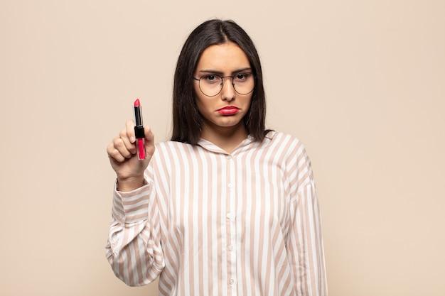 Giovane donna latina che si sente triste e piagnucolona con uno sguardo infelice, piange con un atteggiamento negativo e frustrato