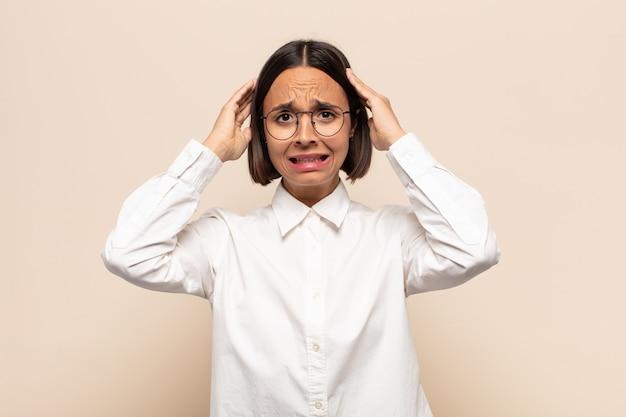 Giovane donna latina che si sente stressata, preoccupata, ansiosa o spaventata, con le mani sulla testa, in preda al panico per errore Foto Premium
