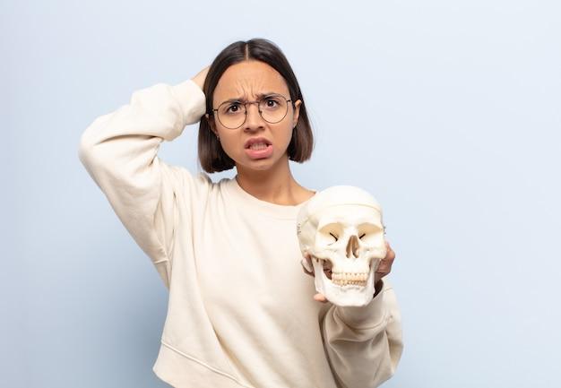 Giovane donna latina che si sente stressata, preoccupata, ansiosa o spaventata, con le mani sulla testa, in preda al panico per errore