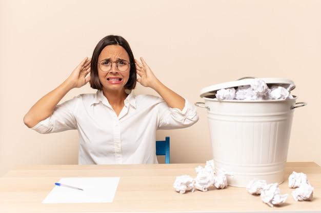 Giovane donna latina che si sente stressata, preoccupata, ansiosa o spaventata, con le mani sulla testa, in preda al panico per l'errore