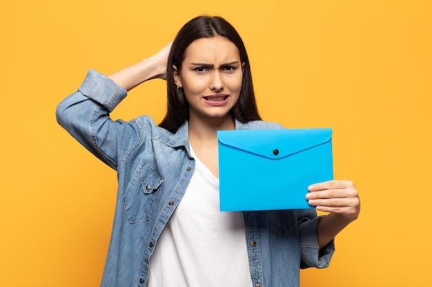 Giovane donna latina che si sente stressata, preoccupata, ansiosa o spaventata, con le mani sulla testa