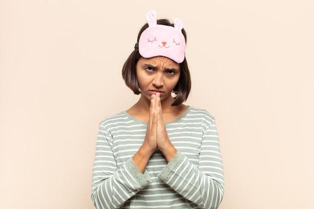 Giovane donna latina che si sente preoccupata, piena di speranza e religiosa, prega fedelmente con i palmi premuti, chiedendo perdono