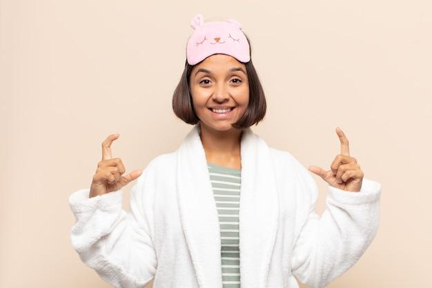 Giovane donna latina che inquadra o delinea il proprio sorriso con entrambe le mani, guardando positivo e felice, concetto di benessere