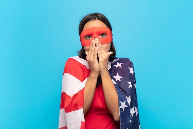 Giovane donna latina felice ed emozionata, sorpresa e stupita che copre la bocca con le mani, ridendo con un'espressione carina