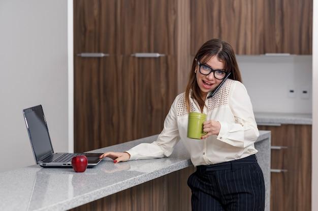 Giovane donna latina che prende una tazza di caffè mentre controlla la posta sul suo laptop dalla cucina